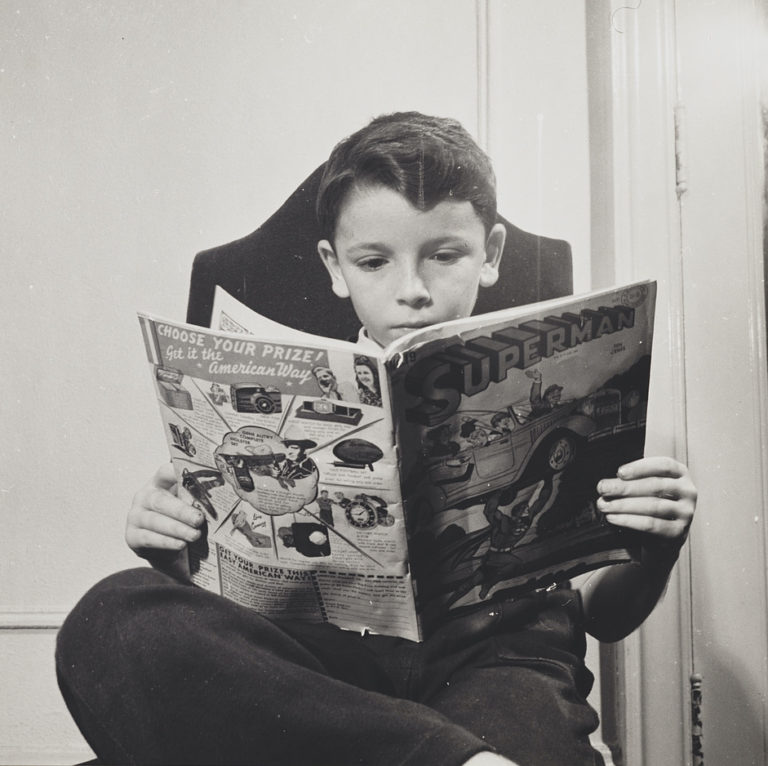 Boy sitting in chair, one foot over the other knee, reading a superman comic book