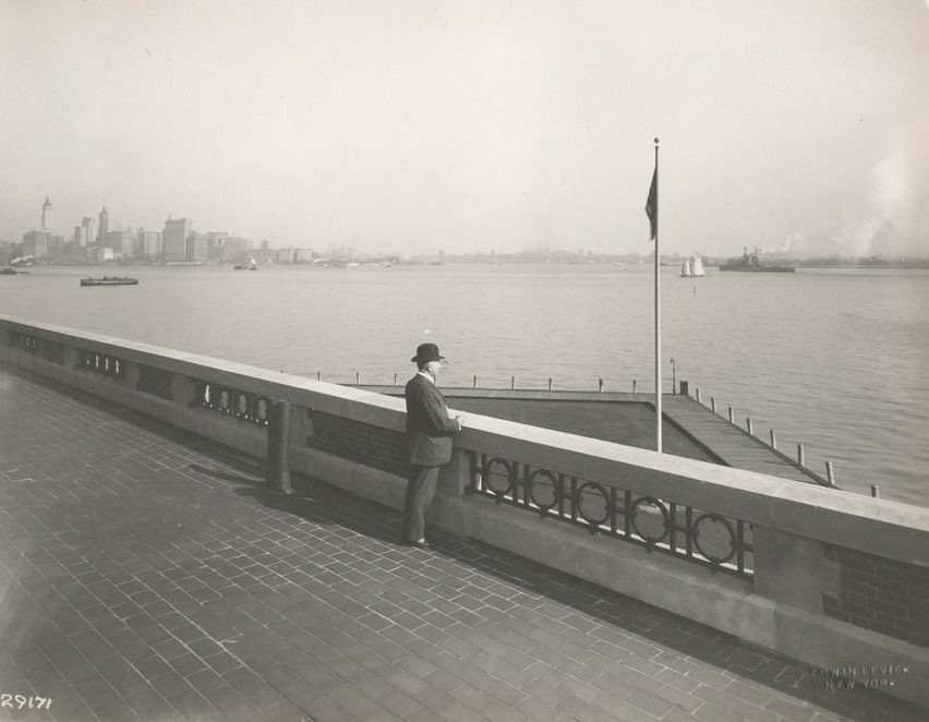 """""""A derby-topped gentleman observing the harbor from the observation roof on one wing of the Immigration Station. The gentleman is possibly William Williams, Commissioner of Immigration at Ellis Island form 1902-5 and 1909-13, from whose estate these photographs came. The New York skyline, showing the nearly-completed Woolworth Building tower, is at the left."""""""