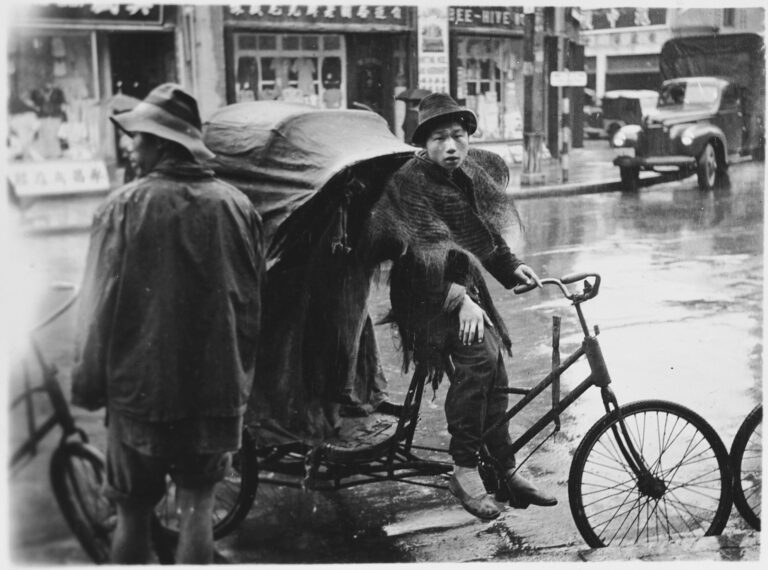Chinese youth on a bicycle passenger cart in the rain by the side of road, perhaps in the company of a couple others with similar rigs because one person and other wheels are visible; shops and and truck in background.