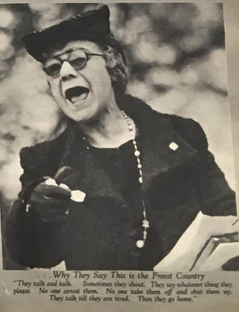 Bespectacled woman with a coat, gloves, and hat giving a speech of some kind. Her mouth is open and her expression is emphatic.